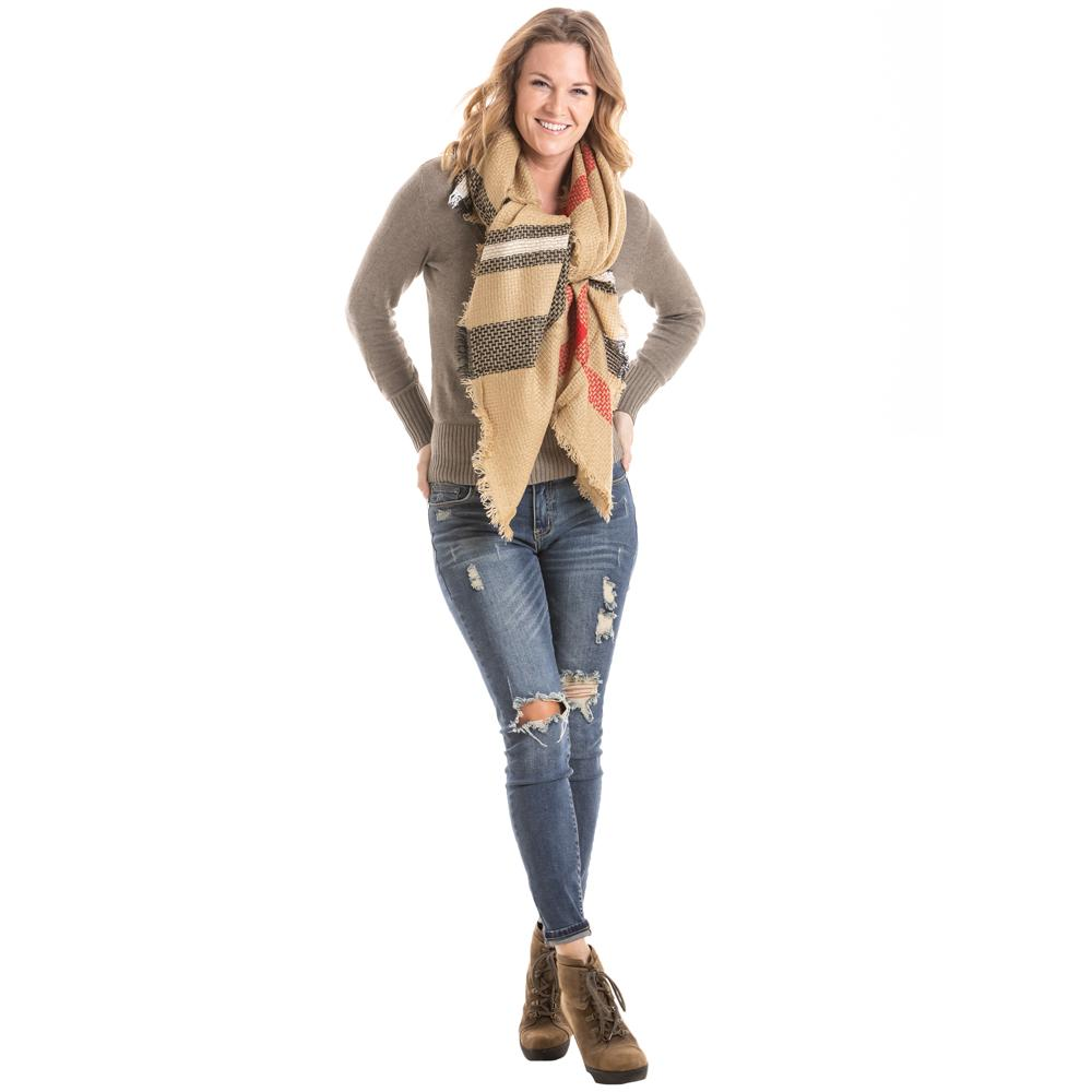 woman in jeans, a long-sleeve top, and a plaid blanket scarf