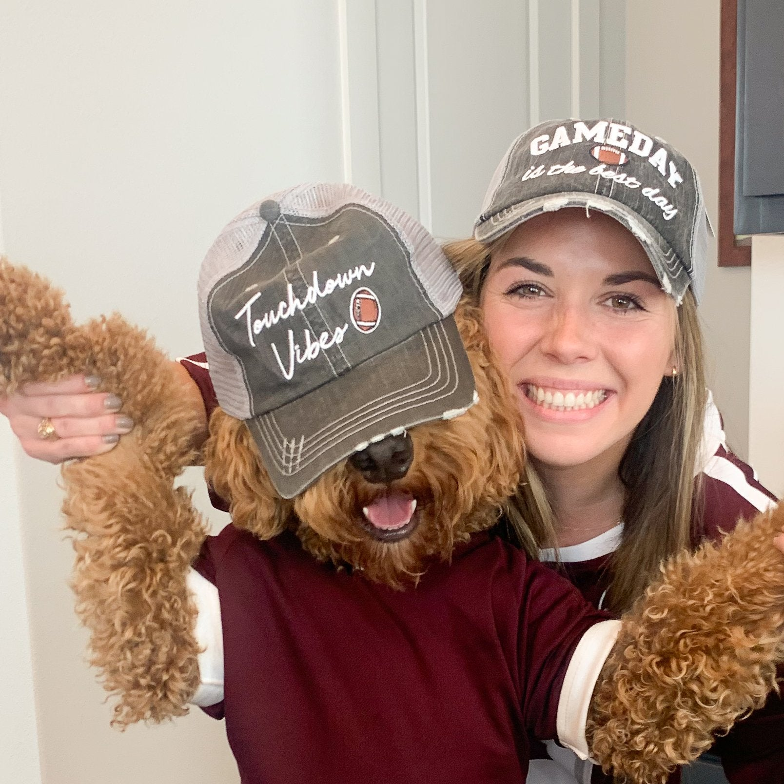 woman and her dog dressed up for a football game in touchdown vibes and game day trucker hats