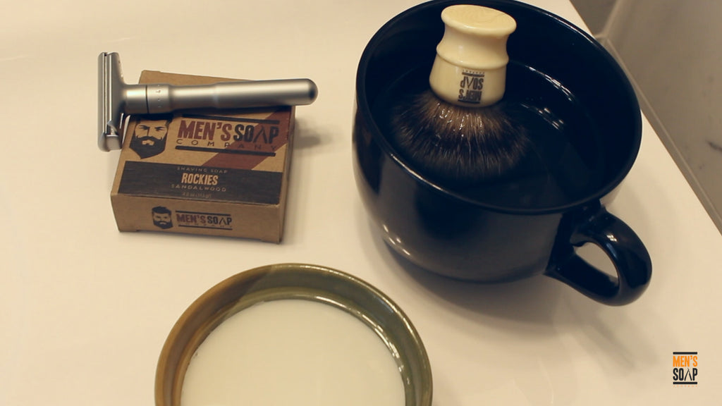 Shaving soap and shaving brush soaking in warm water.