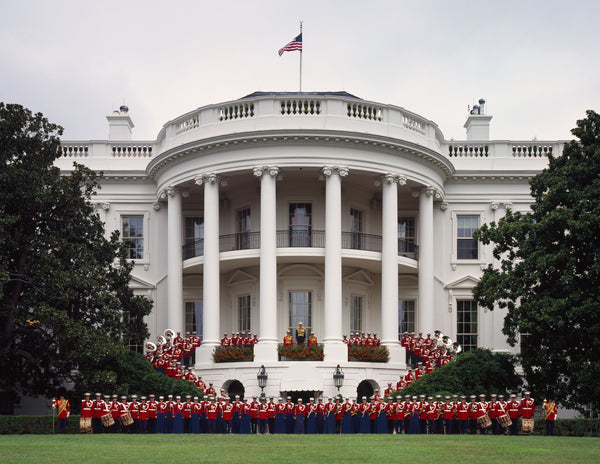 American flag flying on top of the white house with the US Marine Corps Band