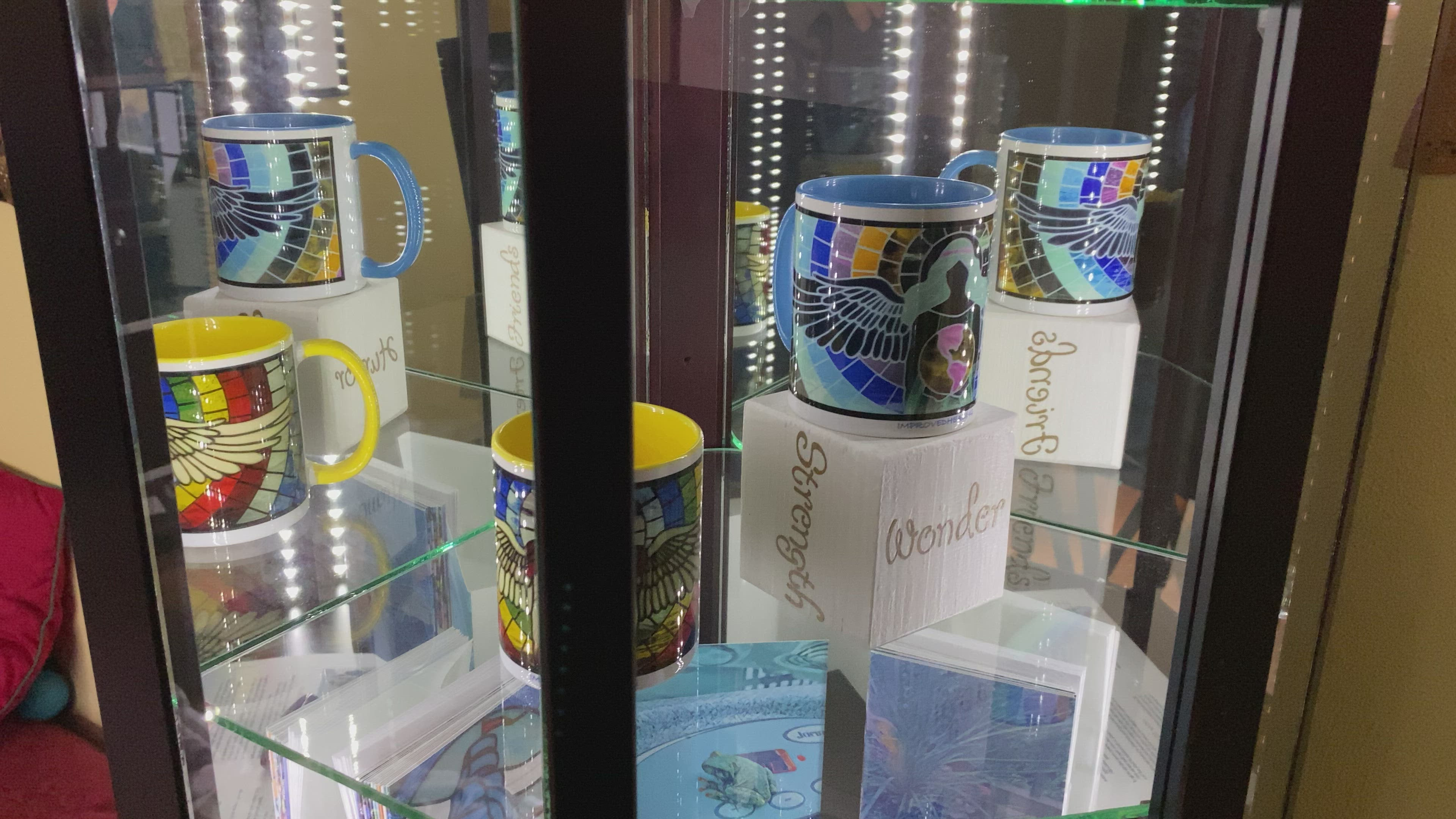 Video of colorful angel mugs in a mirrored cabinet