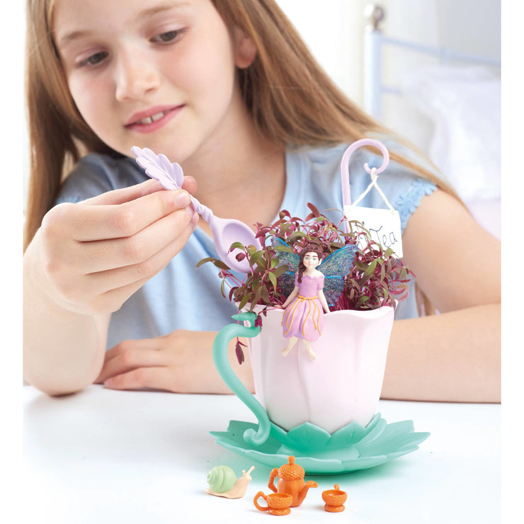 Girl playing with the tea cup fairy garden