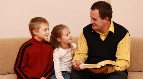 Father teaching his son and daughter about Bible