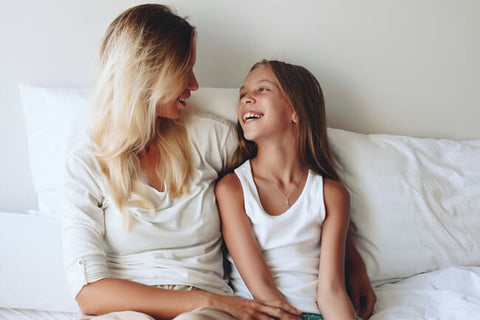 mom and daughter smiling at each other