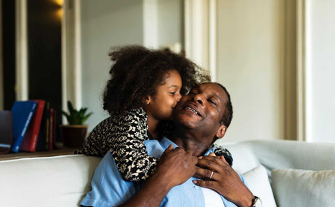 black daughter kissing her dad