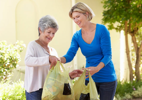 Woman giving some groceries to an old woman