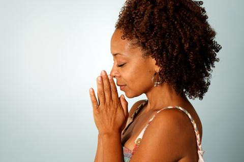 Woman with hands clasped and eyes closed as she prays