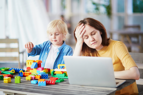 Stressed mom with eyes closed and hand on her forehead in front of a laptop, with content child playing with his Legos beside her.