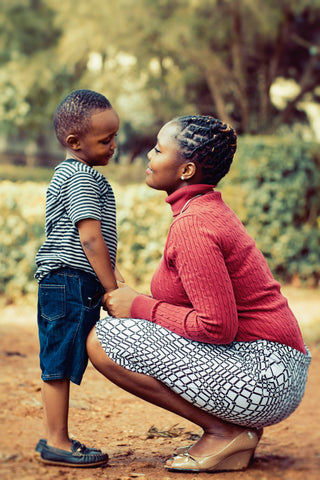 woman in red sweater bending down smiling face to face with young boy
