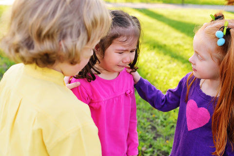 Girls showing compassion by comforting a crying friend