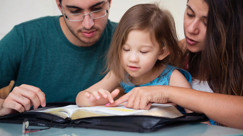 Mom and dad reading the Bible with daughter