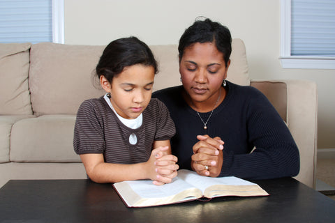 Mom and daughter praying with Bible