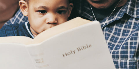 black little boy reading bible with dad