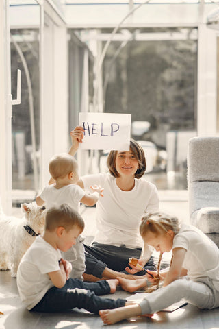 Anxious mom is sitting on the floor with two school-aged children and one toddler (standing), holding a distress HELP sign up.