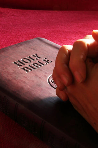 Image of hands clasped on top of the Holy Bible