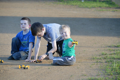 boy with limb differences plays outside with typical older brothers