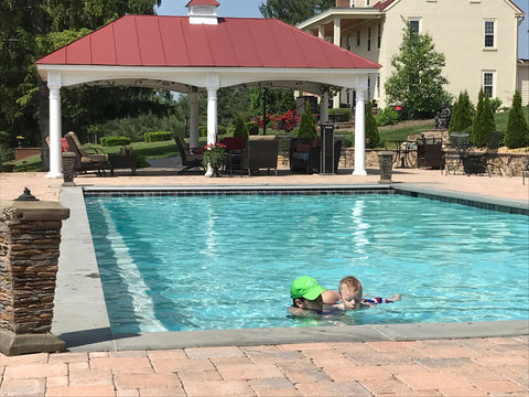 boy with limb differences swims in the pool with help from his mother