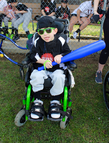 special needs child in a wheelchair holding a baseball bat with eazyhold universal cuff