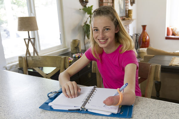 teen girl with a limb difference is sitting at a kitchen counter, using EazyHold to write in a notebook