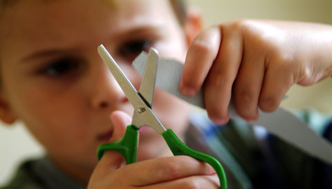 child using bilateral coordination to hold a paper and cut it with scissors