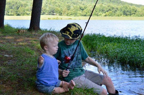 boy with limb differences goes fishing with older typical brother