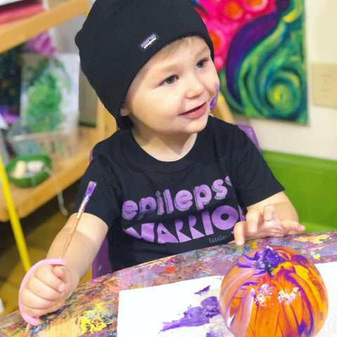special needs toddler painting using an eazyhold daily living aid