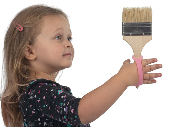 Child grasps paint brush using a silicone gripping aid.