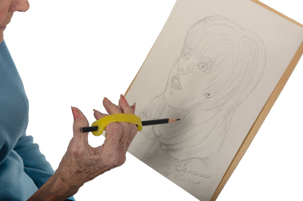 Woman draws with a yellow silicone assistive device to help her grasp the pencil.