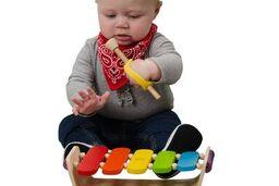 Infant with grip disabilities plays the xylophone using a soft uniersal cuff.