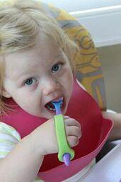 Child with special needs holding a spoon with a green adaptive eating aid