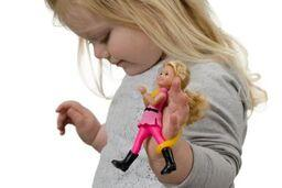 Child with poor motor skills grip holding a doll with a eazy strap on her hand.
