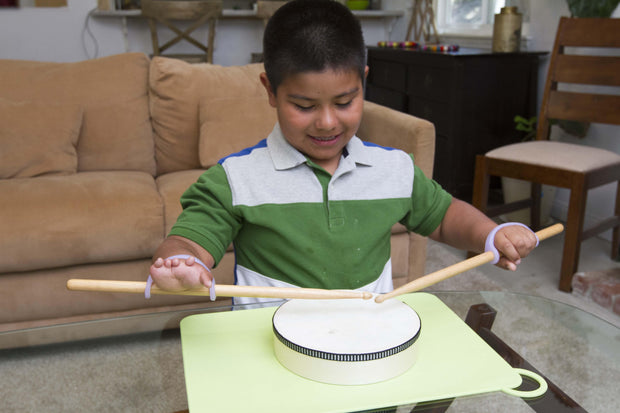 Boy plans the drums with lavender eazyholds on the drumsticks of hands with finger loss