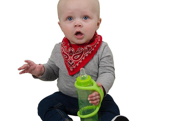 Infant with a disability holds his own bottle with the help of a large green eazyhold grip assist