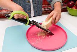 Girl using a green silicone unversal cuff on a cheese grater.