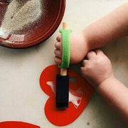 Childs hands with poor motor skills putting glue on a heart with an adaptation.