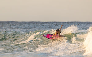 Woman on a surfboard | Em & El Organics Skin Care for Outdoor Adventures
