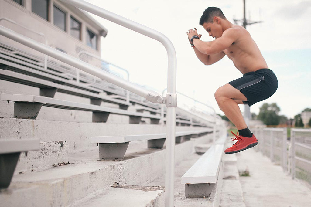 Man Jumping Forward on top of Bleacher bench outside in front of a track and field course