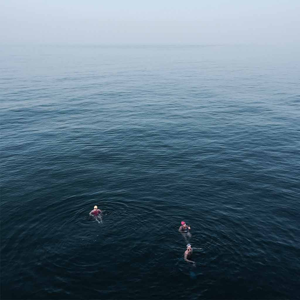 Three people swimming in the ocean