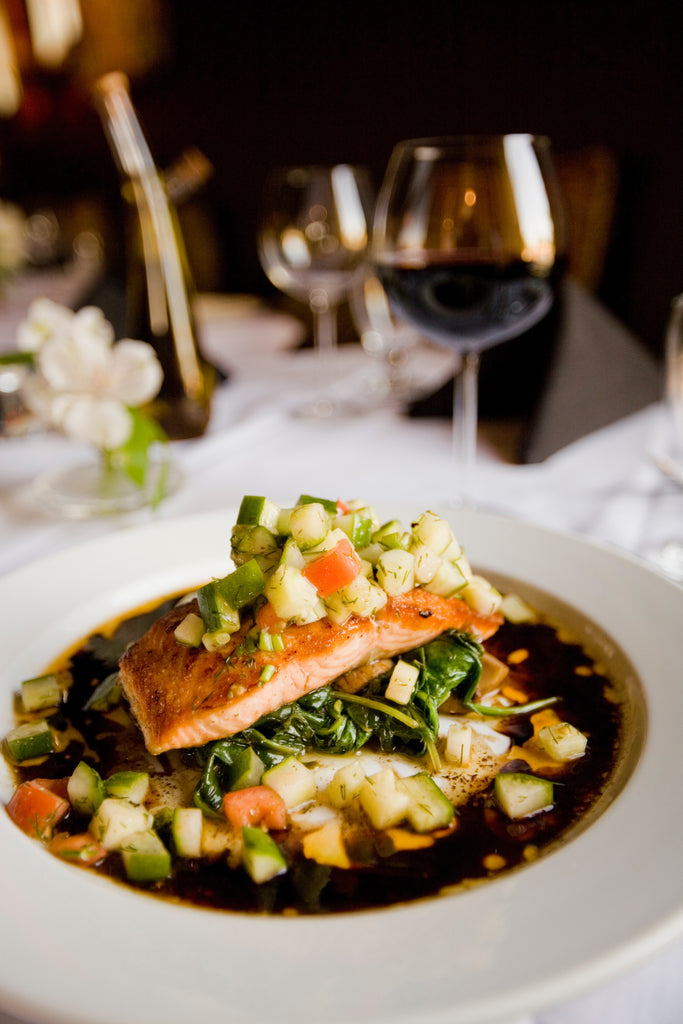 A salmon dinner with a glass of wine