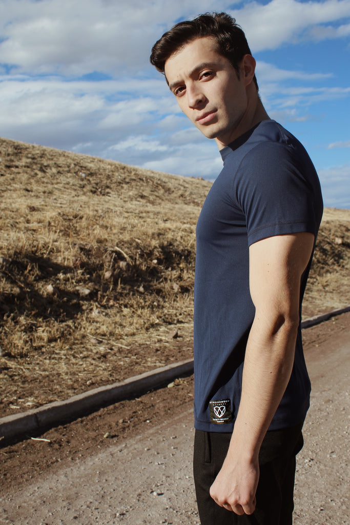 Man standing in front of dried up hill on a sunny day wearing a Navy shirt and Black jogger pants