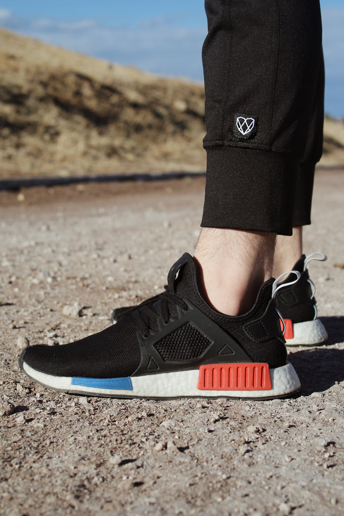 Close up picture of Adidas shoes and Strongbody Apparel black joggers standing on small rocks and in front of a dried hill