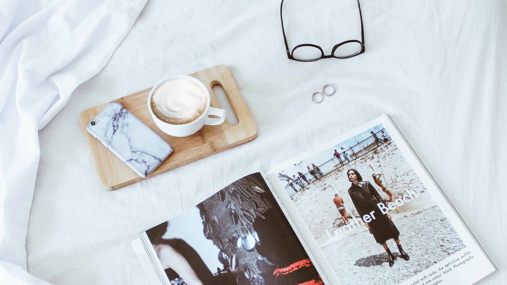 Coffee and magazine on a bed