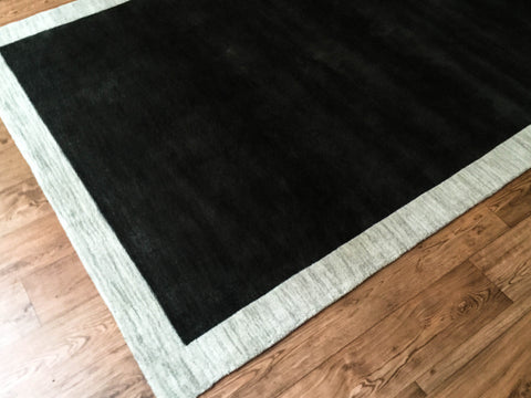 Angelo Surmelis 100-percent wool, hand loomed, rectangular rug features a solid-bordered, black-on-silver pattern for a bold yet under-stated appeal.