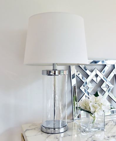 Cylindrical clear glass table lamp with silver trim suits every home decor and interior design.