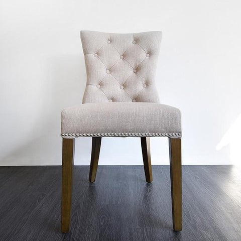 Fleur Dining Chair is adonred with silver nail head trim details, button tufted back rest and fluted angled legs.  Its stylishly oat-coloured upholstery gives any space a light hearted classic mood. It is now available at Finn Avenue, #04-18 Apex@Henderson, Lift Lobby 3, Tel: 6753 3466.