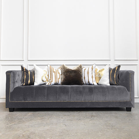 Modern fabric chesterfield sofa in grey velvet and displayed with designer cushions at Finn Avenue showroom in Singapore.