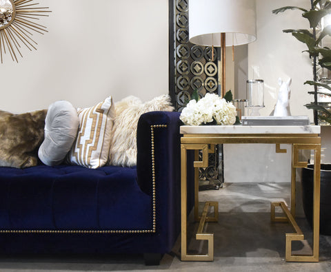 White Marble table top with gold-leaf finish legs displayed next to a purple chesterfield. Luxury furniture and furnishing items available at Finn Avenue Home in Singapore.