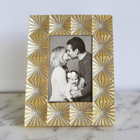 Wooden photo frame with carved fretwork geometric carved designs in glimmer gold hues.