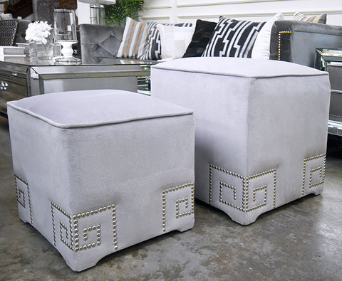 Silver gray velvet footstools with silver nail head trim design.
