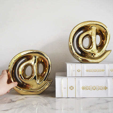 Bookshelf decor with gold symbol bookends for a contemporary home design